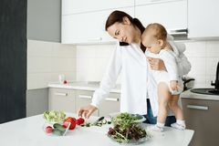 Beautiful young mother cooking healthy dinner, talking on phone and hugging her little son. Baby staying on table near. Mom watching over work with interested stock photo