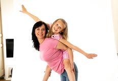 Beautiful young mother and cute charming daughter hugging and playing together. Happy loving family stock photos
