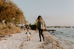 Beautiful Young Mother and Cute Little Boy Son Walking and Enjoying the Nice Outdoor Weather on the Sandy Beach next to the Ocean royalty free stock photography