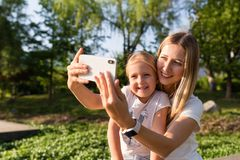 Beautiful young mother and daughter with blonde hair using mobile phone outdoor. Stylish girls making selfie in the park. People stock images