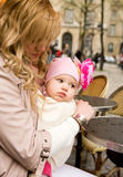 Beautiful young mother with daughter in a cafe. Beautiful young mother with her baby daughter in a Parisian street cafe royalty free stock photos