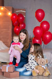 Beautiful young mother and daughter in dresses with wreathes on their hads with colorful baloons in photo studio.  Stock Image