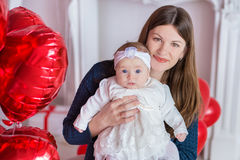 Beautiful young mother and daughter in dresses with wreathes on their hads with colorful baloons in photo studio.  Royalty Free Stock Images