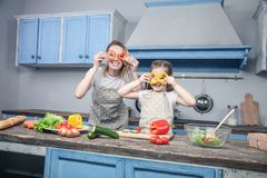 A beautiful young mother and daughter have fun while cooking royalty free stock images