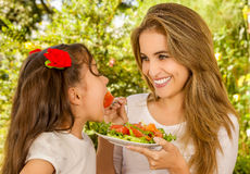 Beautiful young mother and daughter having fun eating a healthy launch Royalty Free Stock Photos