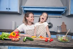 A beautiful young mother and daughter are having fun while preparing their meal in front of the blue kitchen stock images