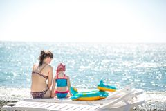 Beautiful young mother and daughter having fun resting on the sea. They sit on the beach with pebbles on a deck chair, their backs. In the frame. Horizontal royalty free stock photo