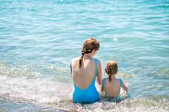 Beautiful young mother and daughter having fun resting on the sea. They sit in the water in the same swimsuit, their backs in the royalty free stock images
