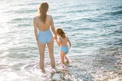 Beautiful young mother and daughter having fun resting on the sea. They stand in the water in the same swimsuit, back in the frame stock image