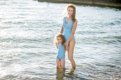 Beautiful young mother and daughter having fun resting on the sea. They stand in the water in the same swimsuit and smile royalty free stock image