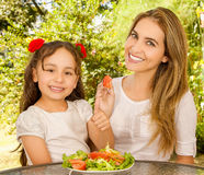 Beautiful young mother and daughter preparing to eat a healthy salad Stock Photography