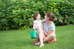 Beautiful young mother daughter smiling each other summer meadow green grass Stock Photos