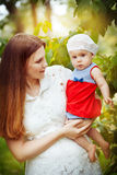 Beautiful young mother and daughter in summer park Stock Photos