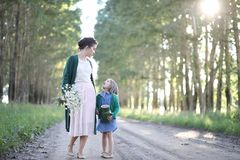 Mother with daughter walking on a road. Beautiful young mother with daughter walking on a rural road Stock Photos