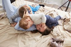 Beautiful young mother dressed in light blue pajama and her two little sons have fun on the bed in the light cozy royalty free stock photo