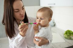 Beautiful young mother feeding little baby boy with spoon while he already eating cookie. Child looks at spoon with royalty free stock images