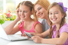 Mother and  girls sitting at  table and using  laptop Stock Images