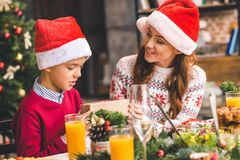 Mother giving christmas gift to son. Beautiful young mother giving christmas gift to excited son Royalty Free Stock Image