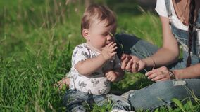 Beautiful young mother giving a small flower to her cute child. Pretty tender mommy and her little son sitting on the