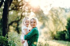 Young mother in nature holding small daughter in the arms. Copy space. Beautiful young mother in green sunny summer nature holding her cute small daughter in royalty free stock images