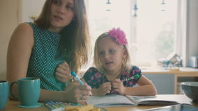 Beautiful young mother is helping her blond little daughter to colour a picture with felt pens. Slow mo stock video footage