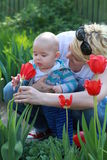 Beautiful young mother and her adorable little boy, playing in the garden Stock Photos