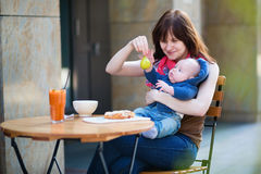 Beautiful young mother with her baby in cafe Royalty Free Stock Image
