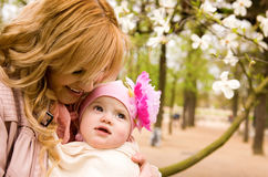 Beautiful young mother with her baby daughter. Outdoors at springtime royalty free stock image