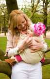 Beautiful young mother with her baby daughter. Outdoors at springtime Stock Photo