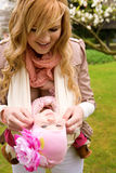 Beautiful young mother with her baby daughter. Outdoors at springtime stock image