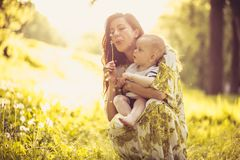Beautiful young mother with her baby Son at nature. Portrait. royalty free stock image