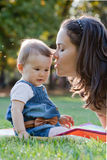 Beautiful young mother and her cute baby. Beautiful young mother and her cute baby in the park Royalty Free Stock Image