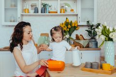 Attractive young woman and her little cute daughter are cooking on kitchen royalty free stock photo