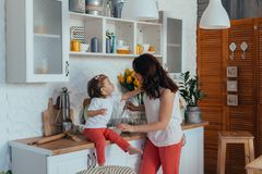 Attractive young woman and her little cute daughter are cooking on kitchen royalty free stock photography