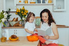 Attractive young woman and her little cute daughter are cooking on kitchen royalty free stock images