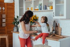 Attractive young woman and her little cute daughter are cooking on kitchen stock photography