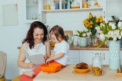 Attractive young woman and her little cute daughter are cooking on kitchen stock images