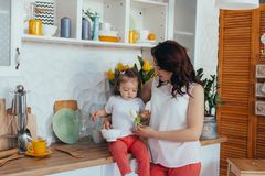 Attractive young woman and her little cute daughter are cooking on kitchen stock image