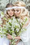 Beautiful young mother with her daughter dressed in spring clothes and wreaths of flowers. Stand on a meadow and snuggling Royalty Free Stock Image