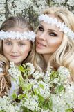Beautiful young mother with her daughter dressed in spring clothes and wreaths of flowers. Stand on a meadow and snuggling Royalty Free Stock Photo