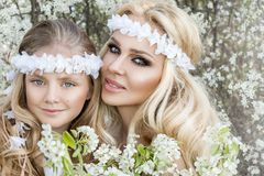 Beautiful young mother with her daughter dressed in spring clothes and wreaths of flowers. Stand on a meadow and snuggling Stock Photos