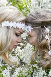 Beautiful young mother with her daughter dressed in spring clothes and wreaths of flowers. Stand on a meadow and snuggling Stock Photo