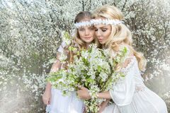 Beautiful young mother with her daughter dressed in spring clothes and wreaths of flowers. Stand on a meadow and snuggling Royalty Free Stock Images