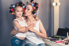Beautiful young mother and her daughter with hair curlers are sp Royalty Free Stock Photography