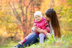 Beautiful young mother with her daughter have fun sitting at autu Royalty Free Stock Images