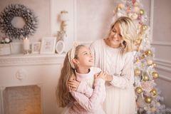 Beautiful young mother with her daughter in the New Year`s interior near the Christmas tree. royalty free stock photos