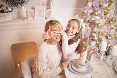 Beautiful young mother with her daughter in the New Year`s interior at the table near the Christmas tree.