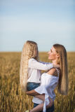 Beautiful young mother and her daughter at the wheat field Royalty Free Stock Photos
