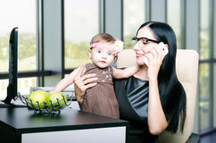 Beautiful young mother with her little cute daughter in the office Royalty Free Stock Images