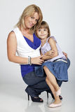 Beautiful young mother and her little daughter. Full length portrait of two, beautiful young mother and daughter, smiling, studio image Royalty Free Stock Image
